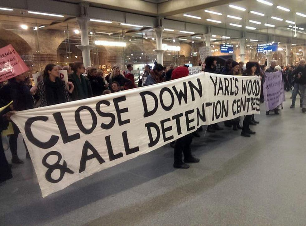 Protesters hold up a banner calling for the closure of the Yarls Wood detention centre at Kings Cross St Pancras station