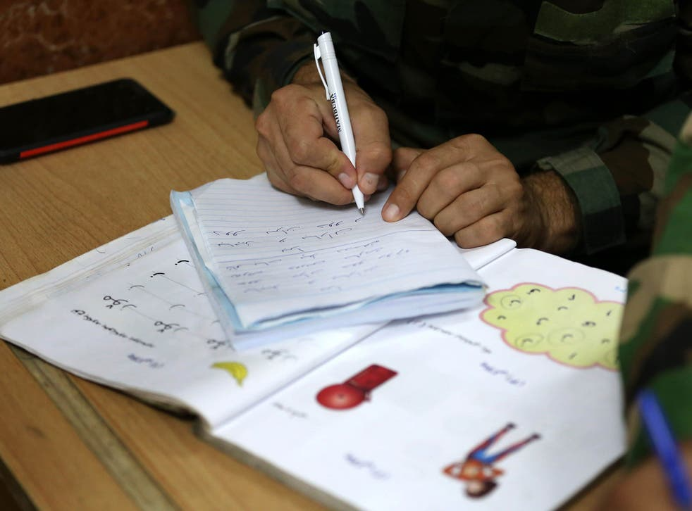 An Iraqi Kurdish Peshmerga fighter attends a night school in Iraq. The location of the classes is a closely guarded secret in order to protect the students
