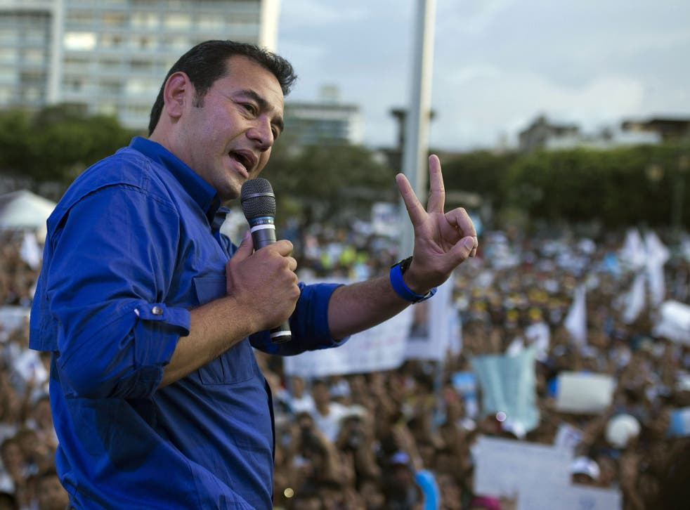 In this Thursday, Oct. 22, 2015 photo, Jimmy Morales, the National Front of Convergence party presidential candidate, gives a victory sign as he speaks to supporters during a campaign rally in Guatemala City
