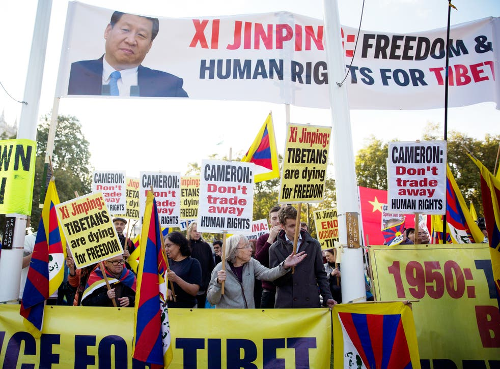 Human rights demonstrators stand beneath a protest banner bearing an image of Chinese President Xi Jinping on Parliament Square outside the Houses of Parliament, where he was giving a speech in London