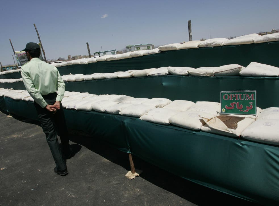 Iranian policeman guards the 3000 kilograms of opium seized from the drug smugglers in the southeastern city of Zahedan
