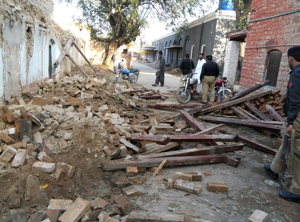 Pakistani policemen stand beside debris of collapsed houses after an earthquake in Kohat