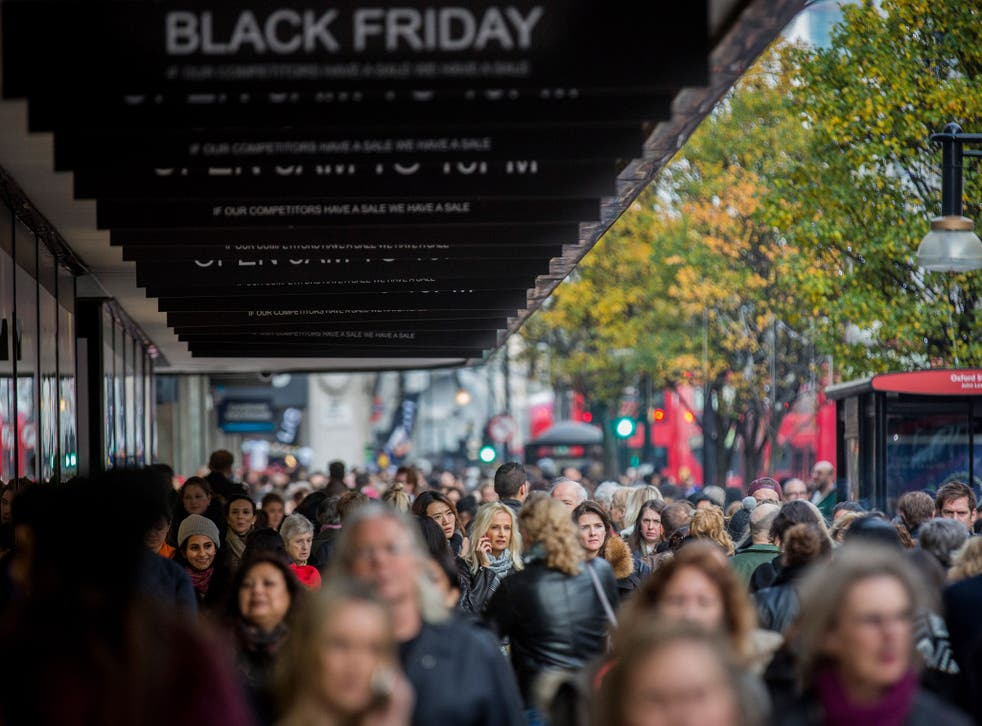 People walk past a shopfront on Oxford Street advertising 'Black Friday' discounts on November 28, 2014 in London, England