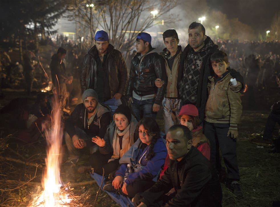 Kawphar Zangana, back right holding his sons, is surrounded by friends and family trying to stay warm while waiting in no-man's-land on the Slovenian border