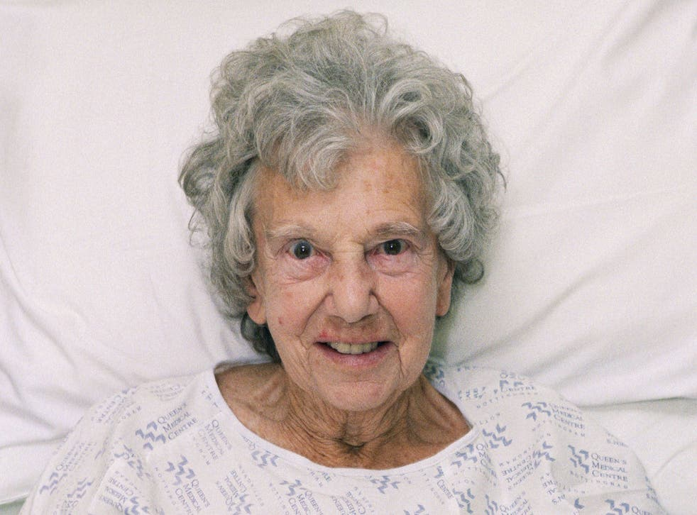 An elderly woman sitting up in a hospital bed on waits to be seen by a nurse