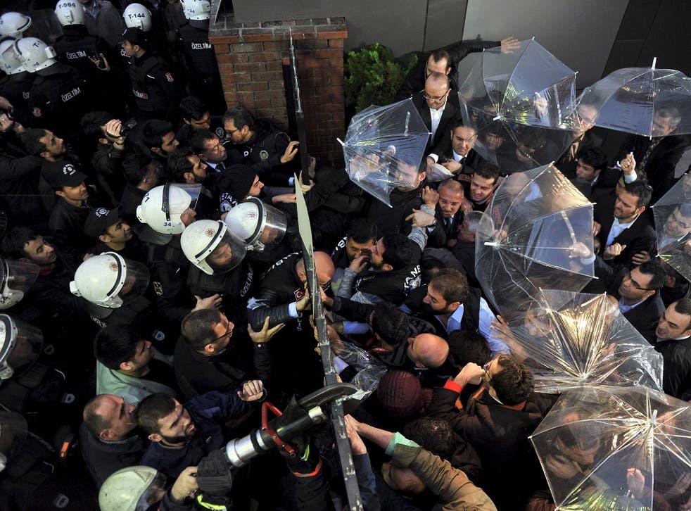 Employees block the door as riot police try to enter Kanalturk and Bugun TV building in Istanbul, Turkey, October 28, 2015