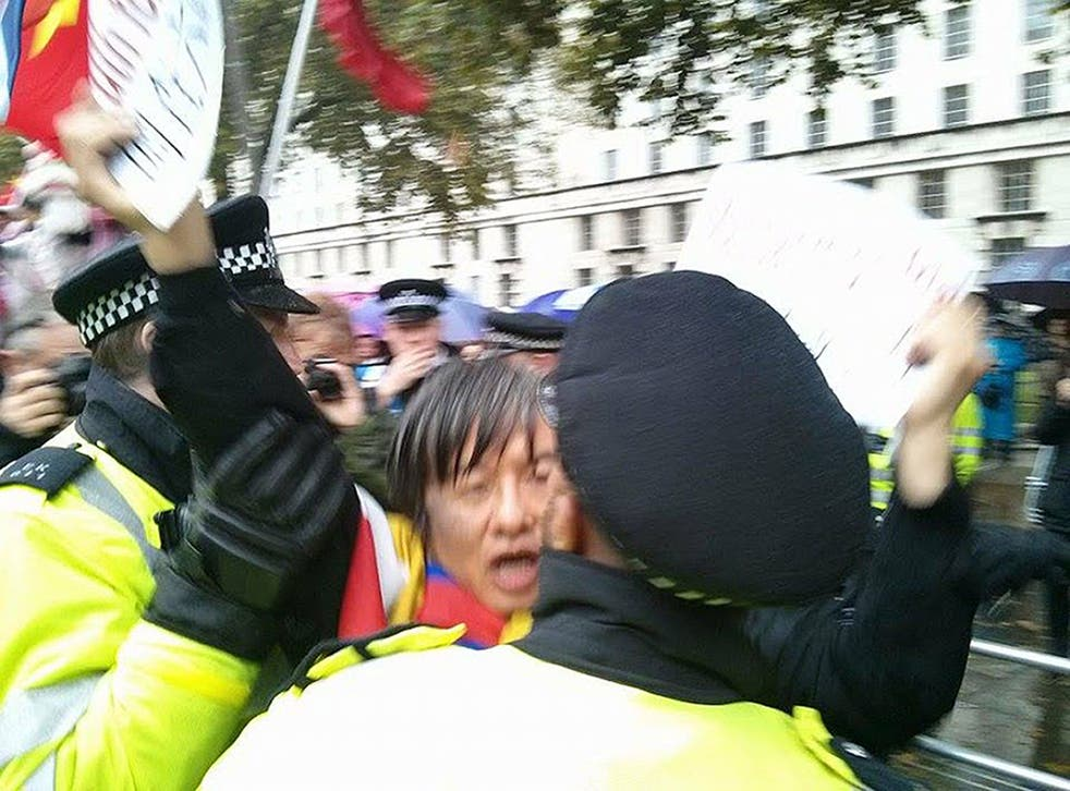 Chinese democracy activist and Tiananmen Square survivor Shao Jiang being led away by police officers. The police were accused of mishandling the 47-year-old away from a human rights protest before raiding his home