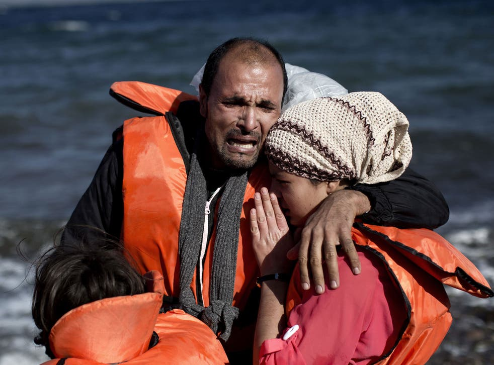A family reacts after arriving, with other refugees and migrants, on the Greek island of Lesbos, on October 28, 2015,