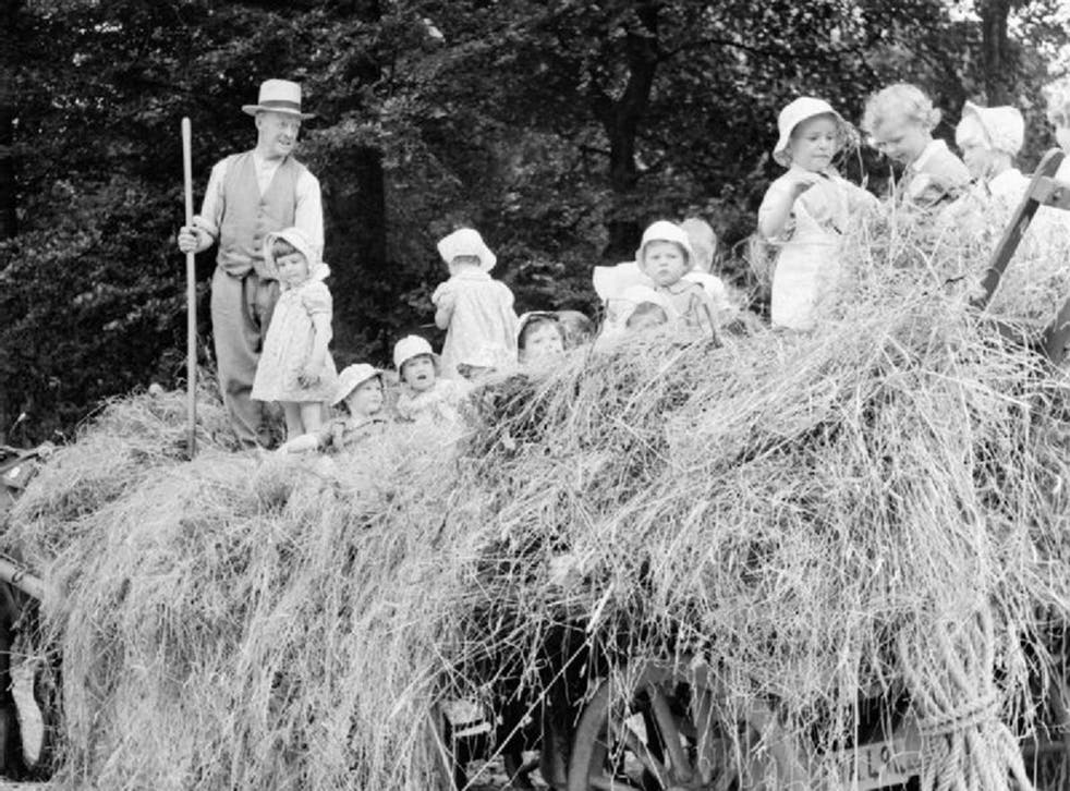 A group of young evacuees sit on a hay cart outside Chapel Cleeve Nursery in Washford Somerset