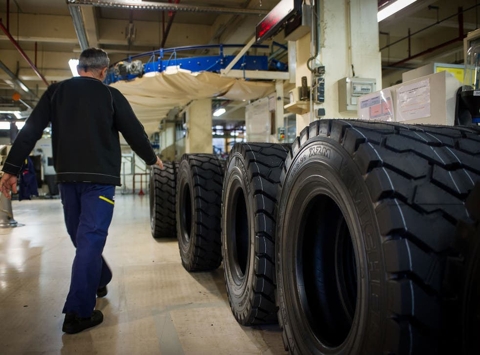 A worker controls truck tyres in the Michelin factory on december 18, 2014 in Joué-lès-Tours, central France
