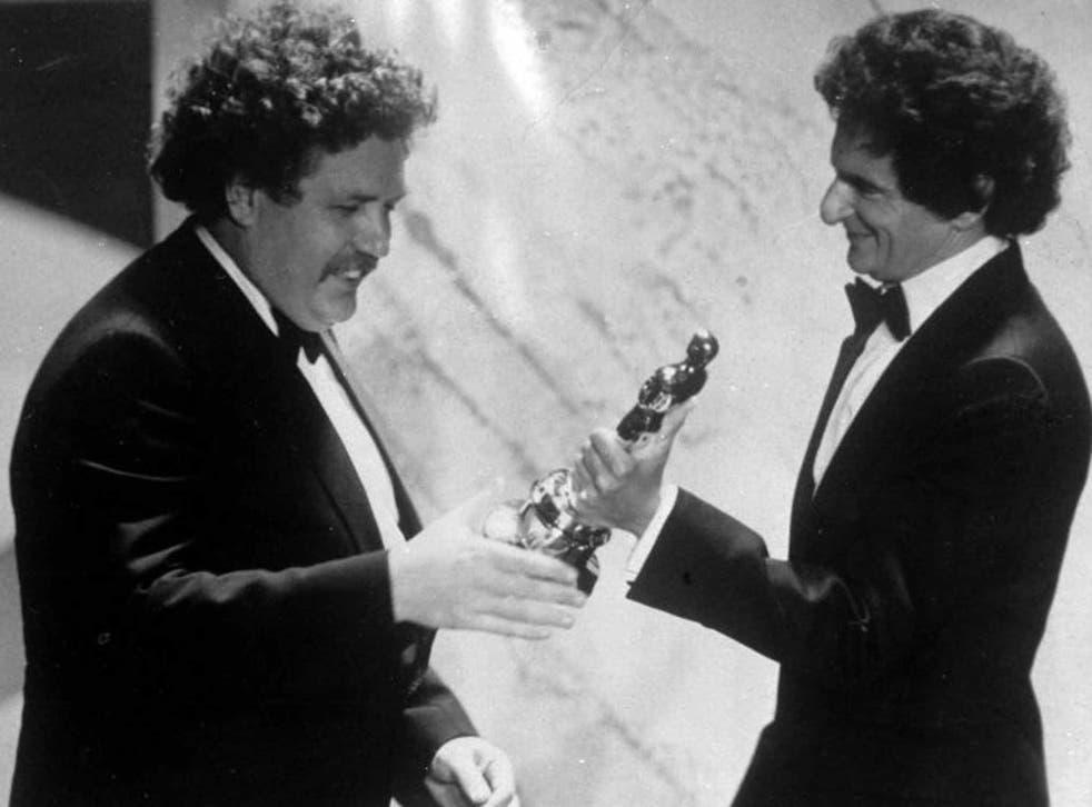 Welland accepts his Oscar for Best Original Screenplay from the novelist Jerzy Kosinski in 1982