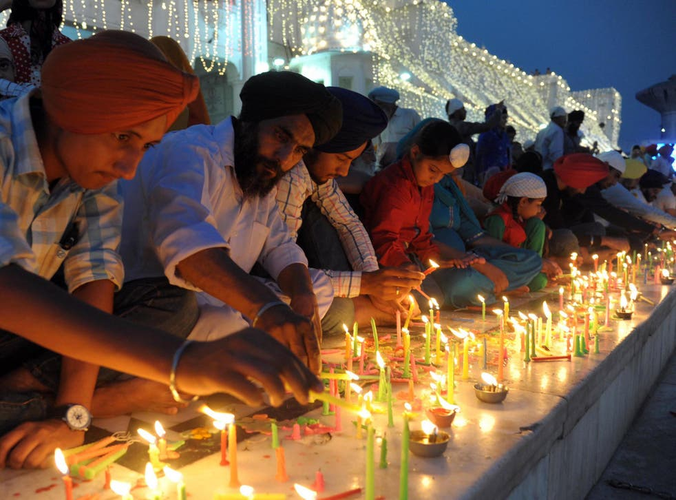 Indian Sikh devotees light candles on the occasion of Bandi Chhor Divas, or Diwali, at the illuminated Golden Temple in Amritsar, India