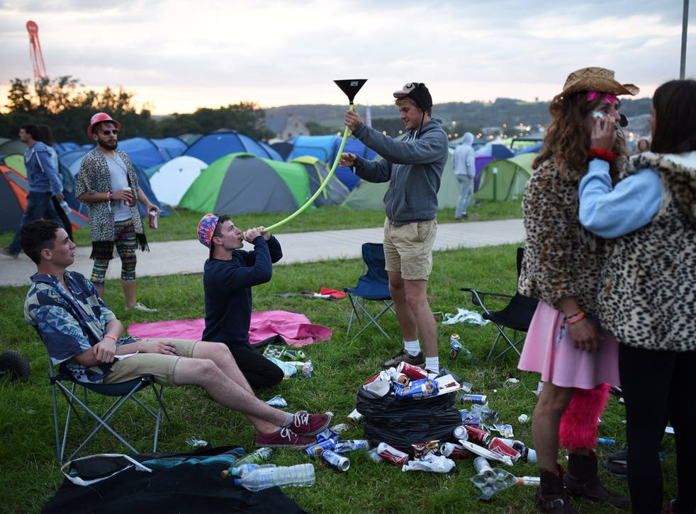 Festival attendees enjoy a drink at Glastonbury Festival (Getty)
