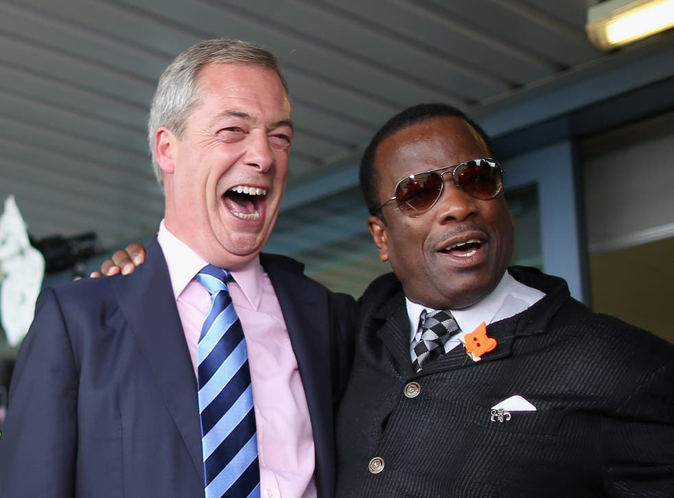 Nigel Farage poses for a photo with the UKIP delegate Winston McKenzie