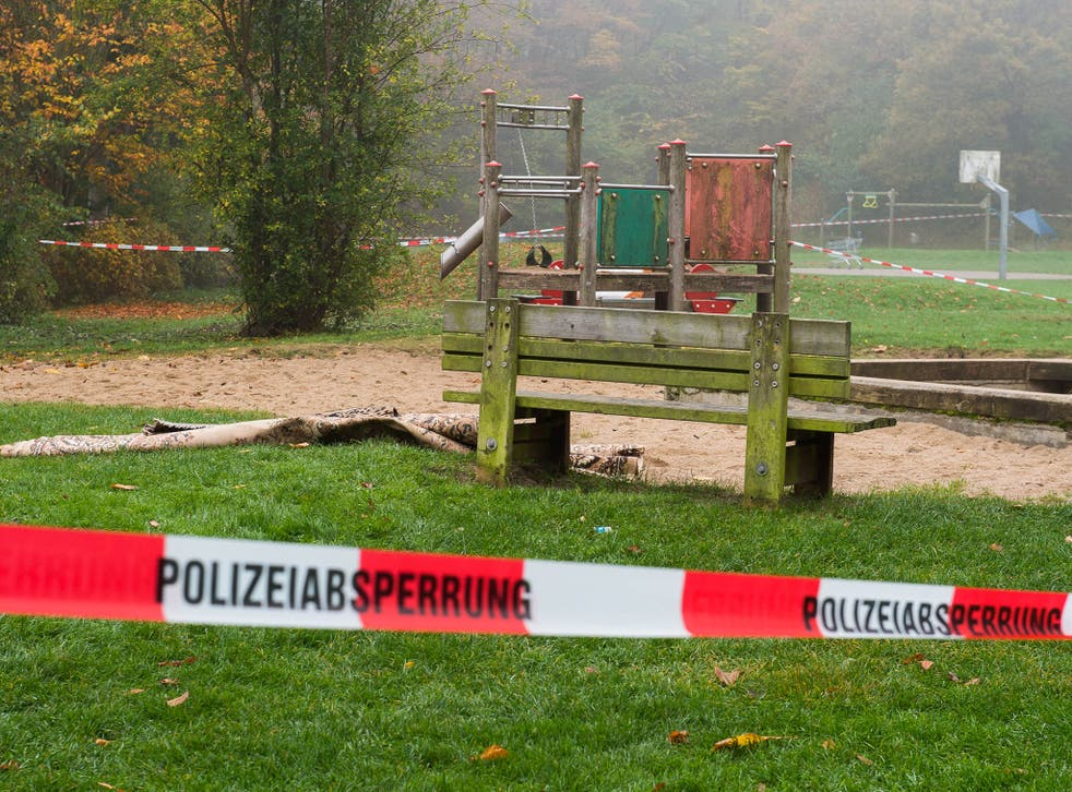 Police tape cordons off the playground bench where the woman burst into flames, in Flensburg, Germany