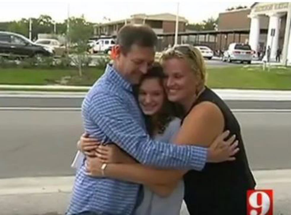 Ella Fishbough, 14, receives a hug from her parents