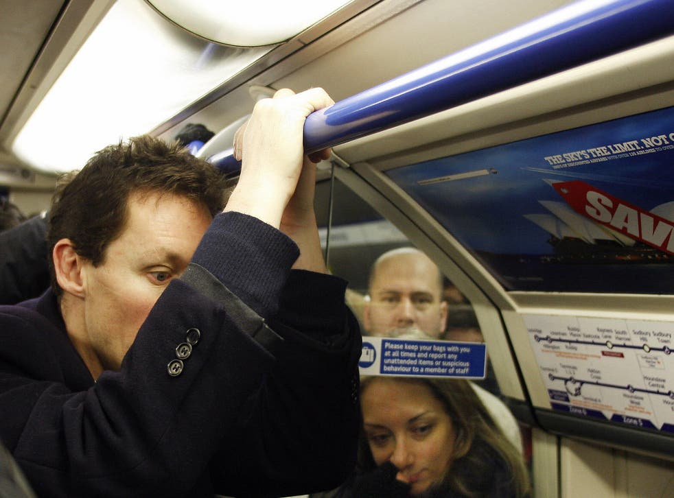 A man hangs onto a rail on the London Underground