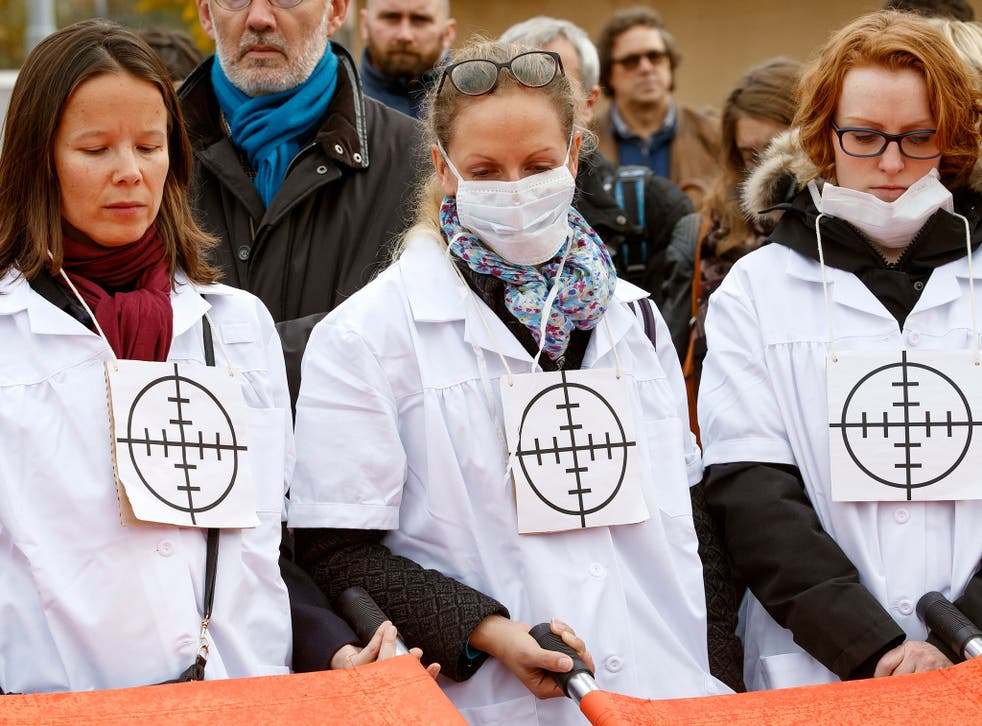 MSF staff wear targets on their chests during a protest in Geneva, one month on from the air strike