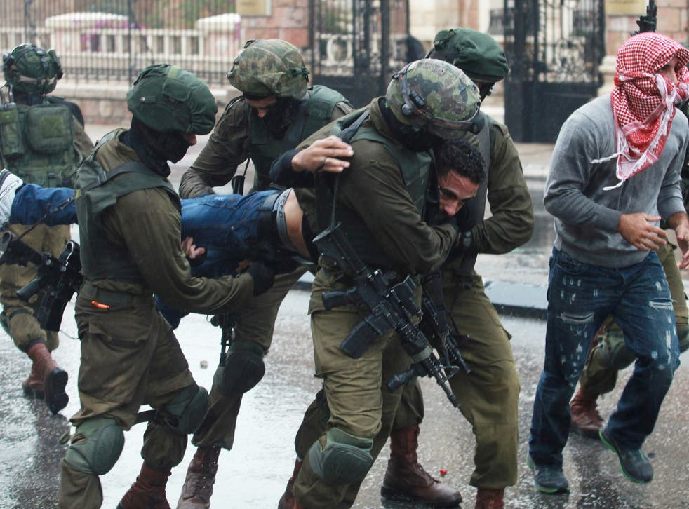 Israeli soldiers and undercover security personnel detain a Palestinian protester during clashes in the West Bank city of Bethlehem