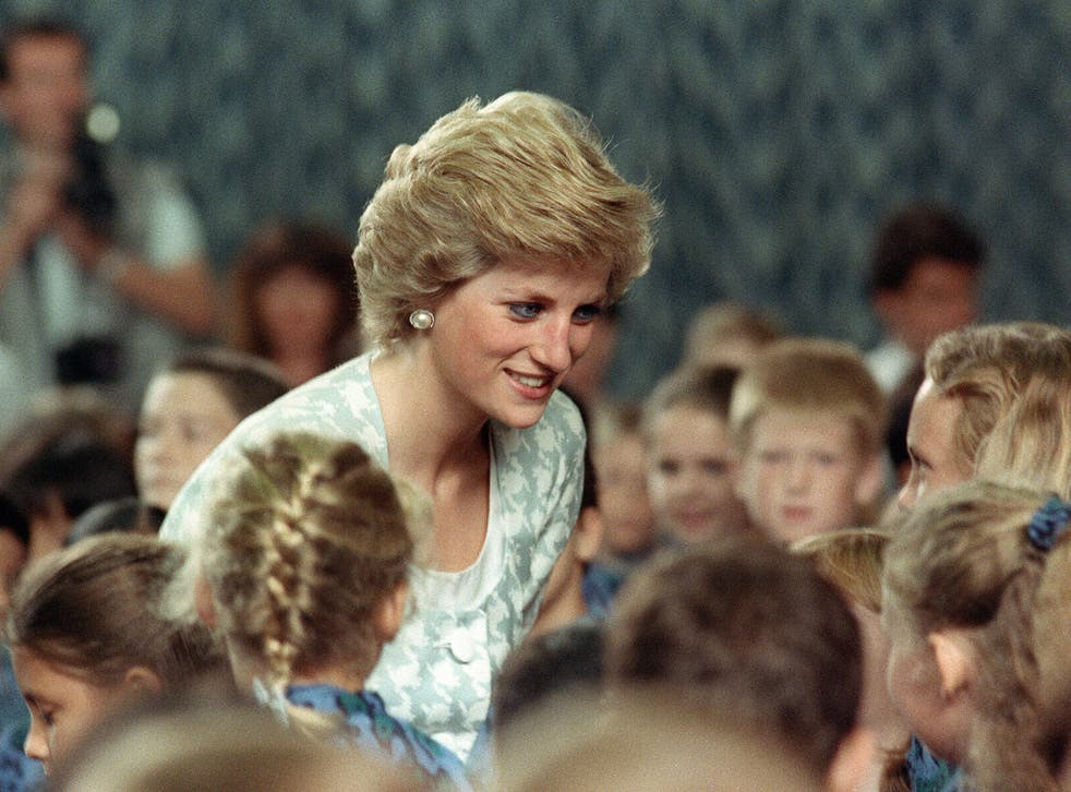 Diana, Princess of Wales listening to children during her visit to the British international school