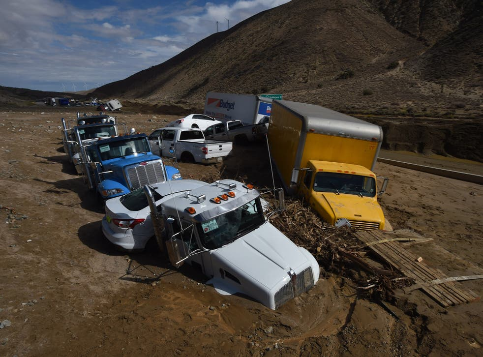 Vehicles are stuck on a road after being trapped by a mudslide on California Highway 58 in Mojave, California on October 16, 2015