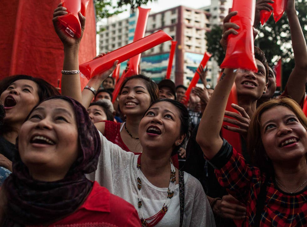 Supporters cheer as they wait for results at a National League for Democracy rally in Rangoon
