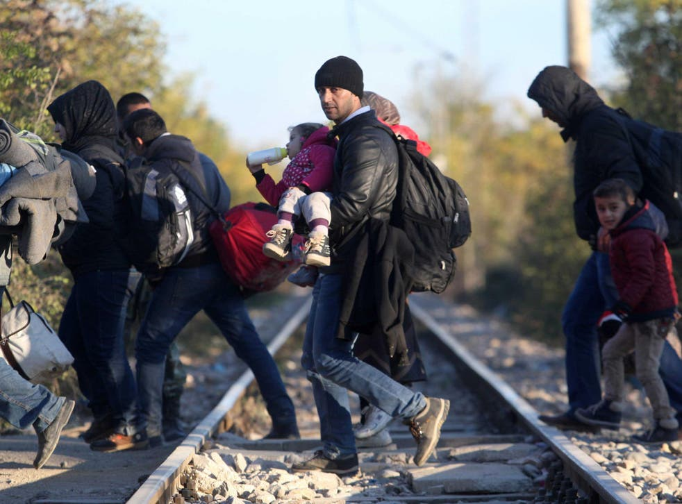 Refugees cross the border from Greece to Macedonia near the village of Idomeni