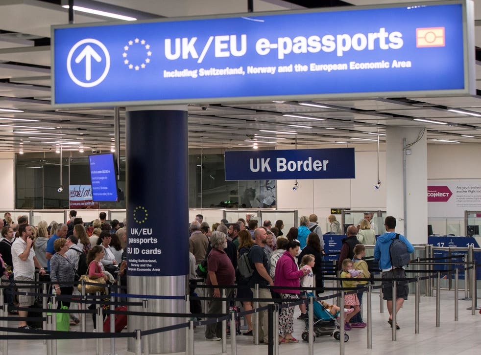 Passengers at Gatwick Airport queue to have their passports checked upon entering the UK