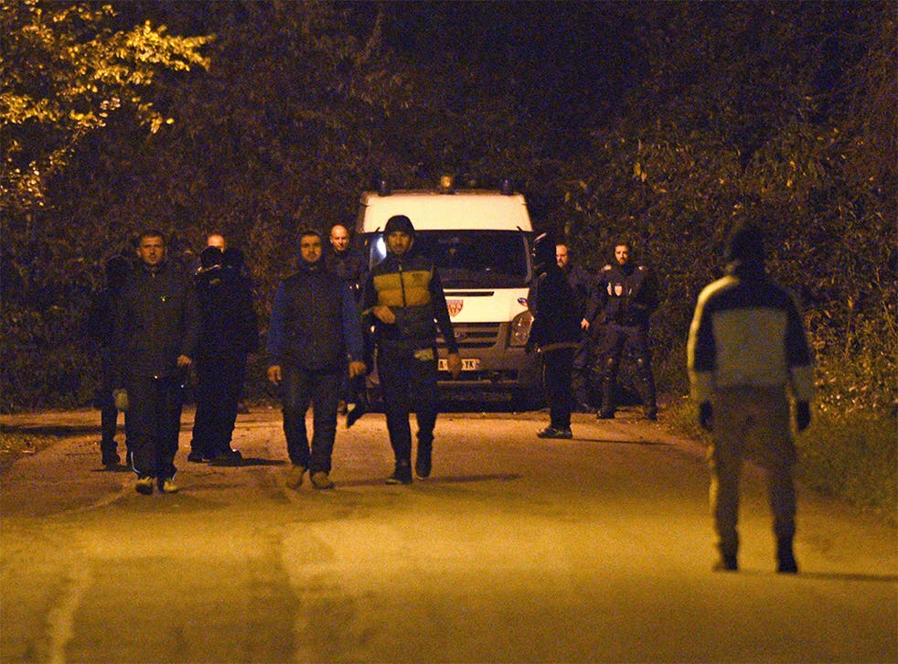 Migrants walk past French CRS police forces in Calais