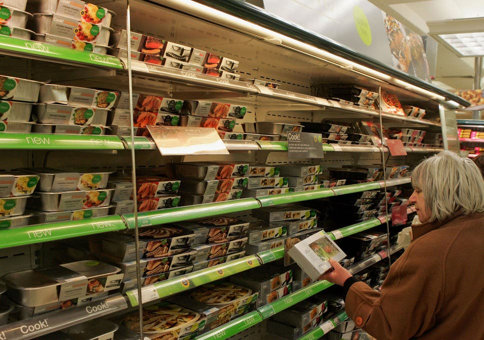 147d5a2ba491 A woman examines a product on display as she shops in the food department of  a