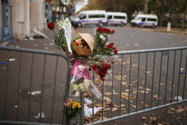 Flowers lie in front of a police cordon where concert-goers were killed at the Bataclan theatre in Paris