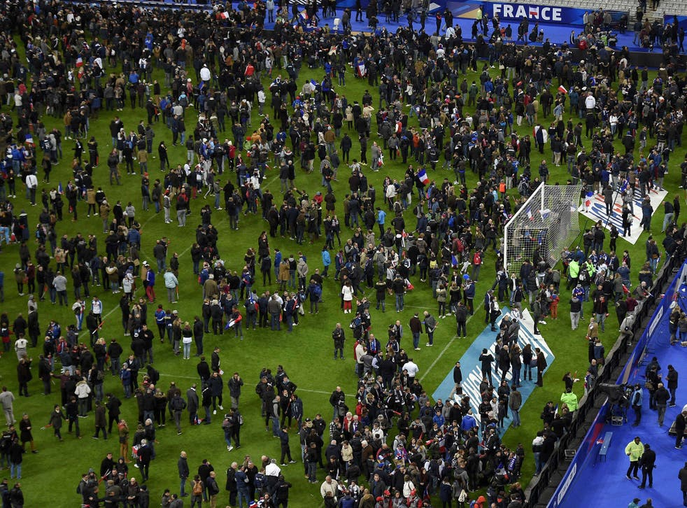 Fans at the Stade de France gather on the pitch after the Paris attacks
