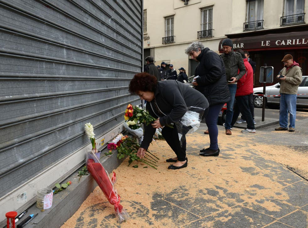 A woman places Flowers outside Le Petit Cambodge restaurant the day after the deadly attacks