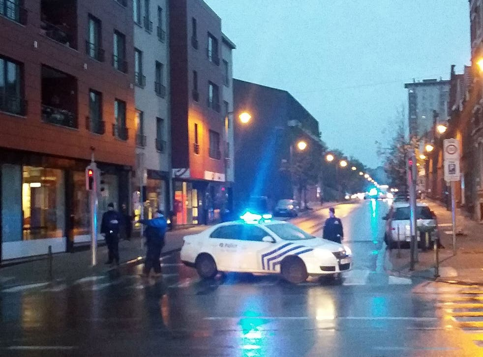 Belgian police blocking a street during a police raid in connection with the attacks in Paris, in Brussels' Molenbeek district on 14 November