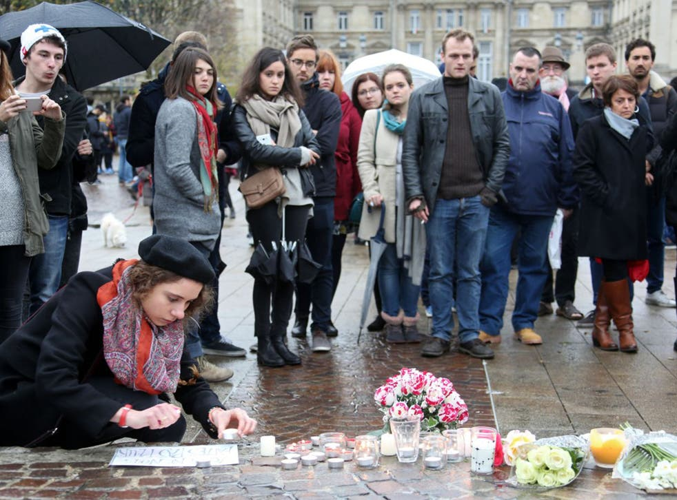 People light candles at a makeshift memorial in Lille, northern France,to pay tribute to the victims of the terror attack in Paris
