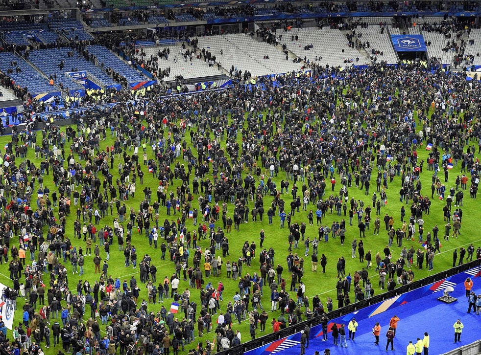 Spectators gather on the Stade de France pitch anxious to discover what had happened outside