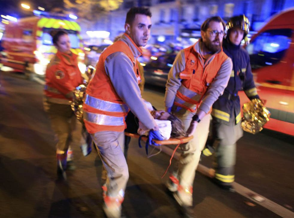 A woman is evacuated from the Bataclan theater after a shooting in Paris