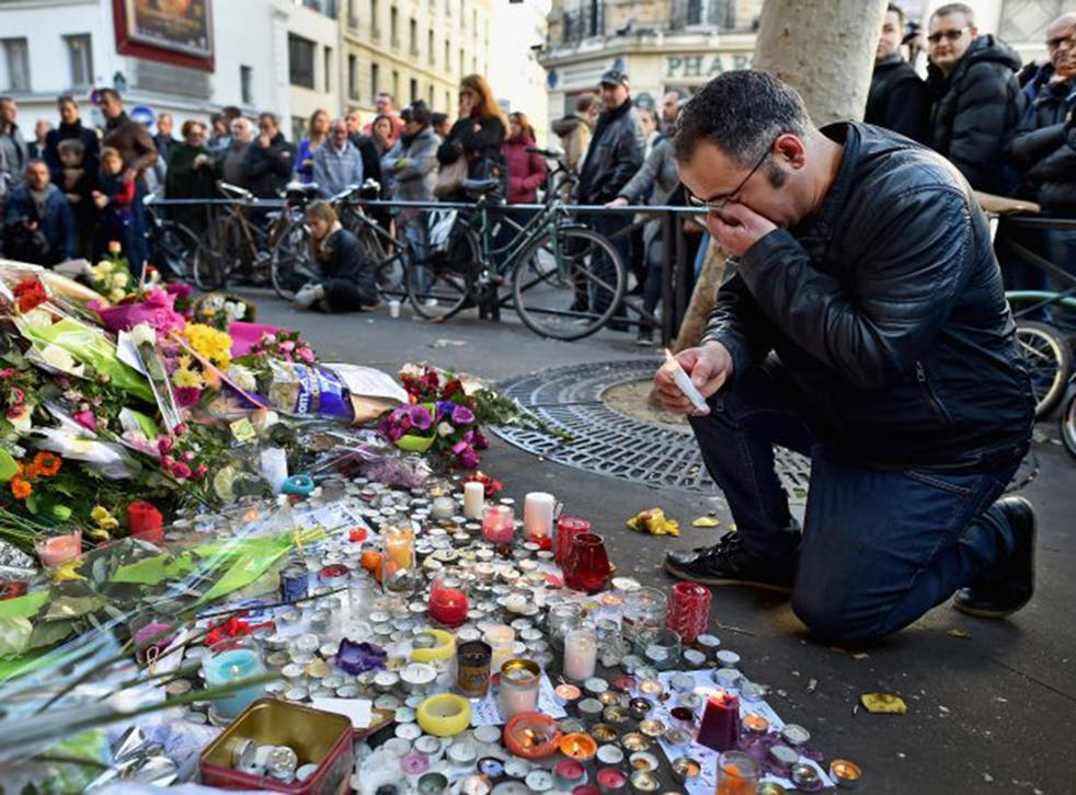 Members of the public gather to lay flowers and light candles at La Belle Equipe restaraunt on Rue de Charonne following Friday's terrorist attack