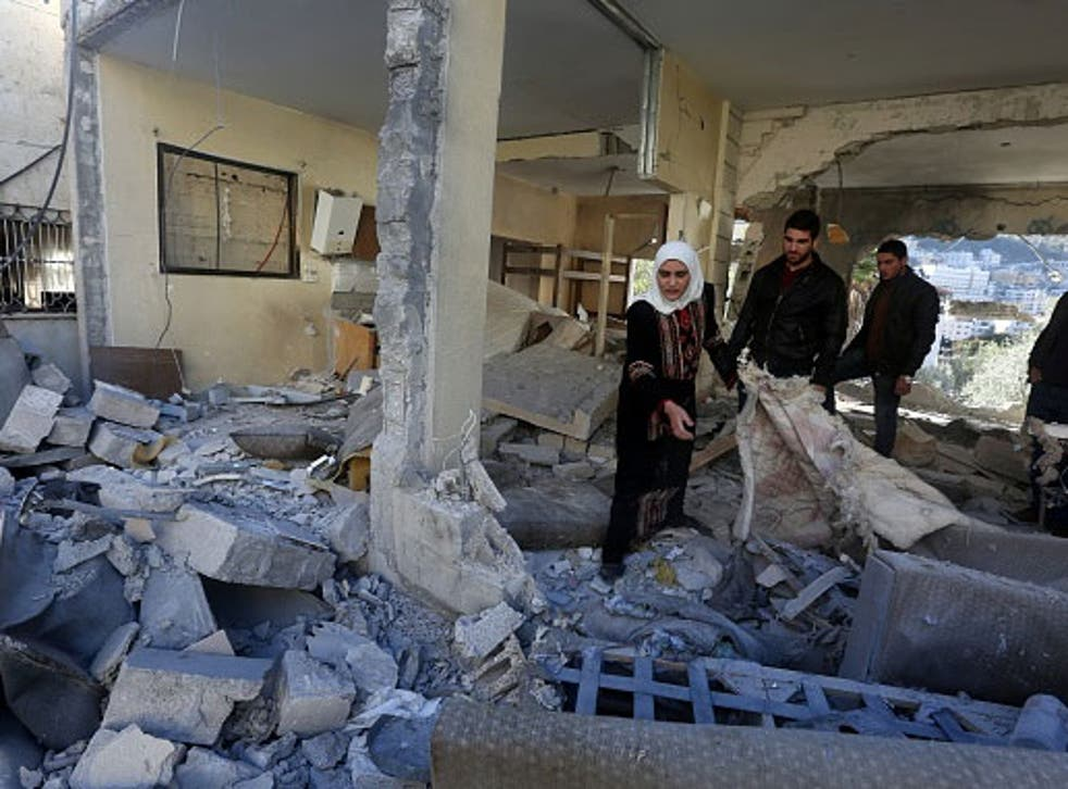 Palestinians look at the rubble of the house of a member of the group accused of killing a couple on October 1, the day after it was destroyed by Israel in the West Bank city of Nablus on November 14