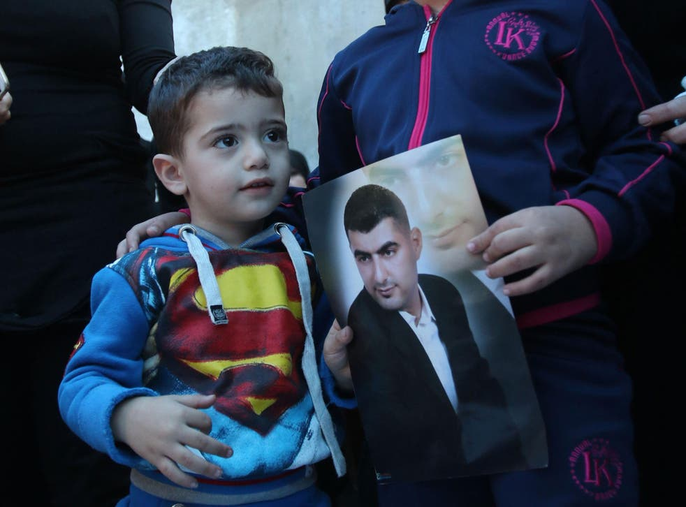 Adel Termos's son stands next to a picture of his father at his funeral