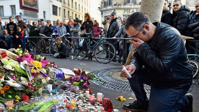 Members of the public gather to lay flowers and light candles at La Belle Equipe restaraunt on Rue de Charonne in Paris