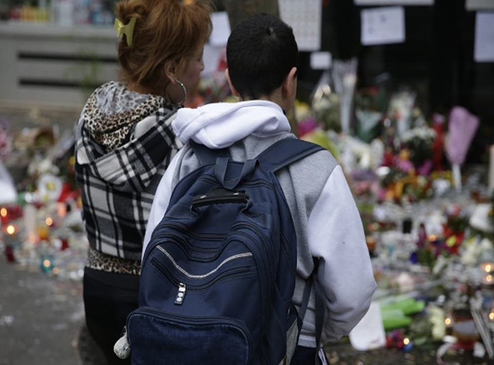 A woman and a her son spend a moment mourning the dead at the site of the attack at the Cafe Belle Equipe on rue de Charonne this morning, prior to going to work and school