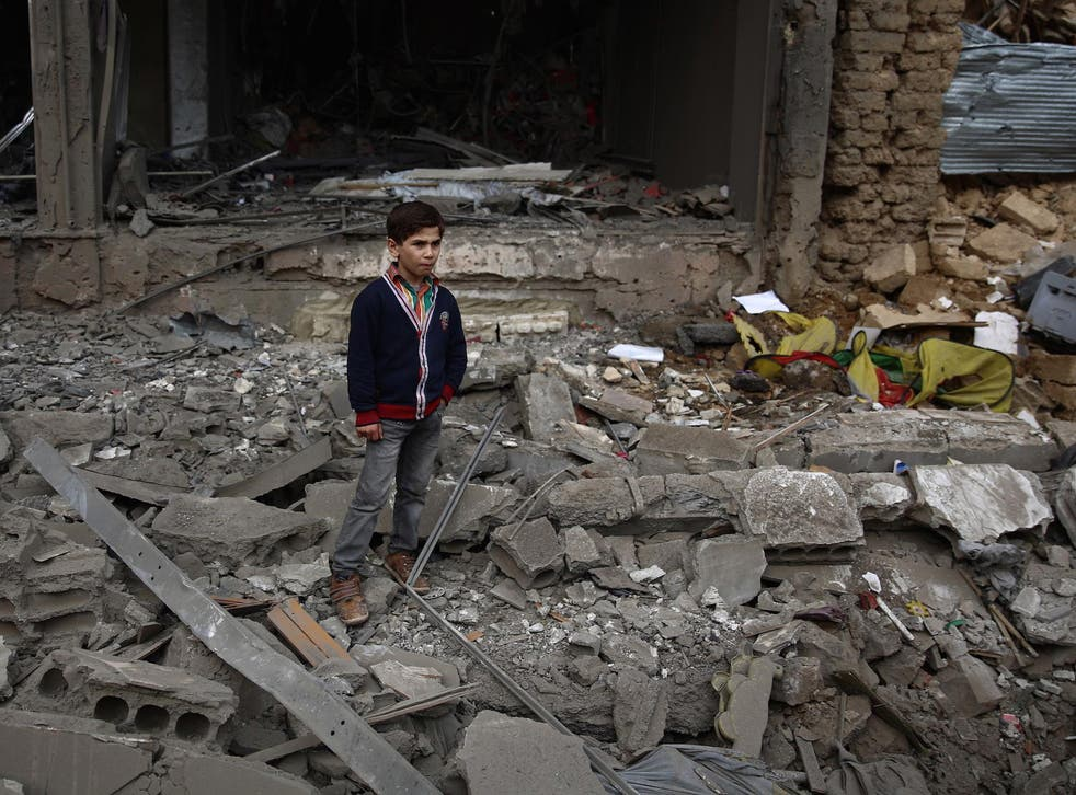 A young boy stands amid debris following a reported air strike in Syria