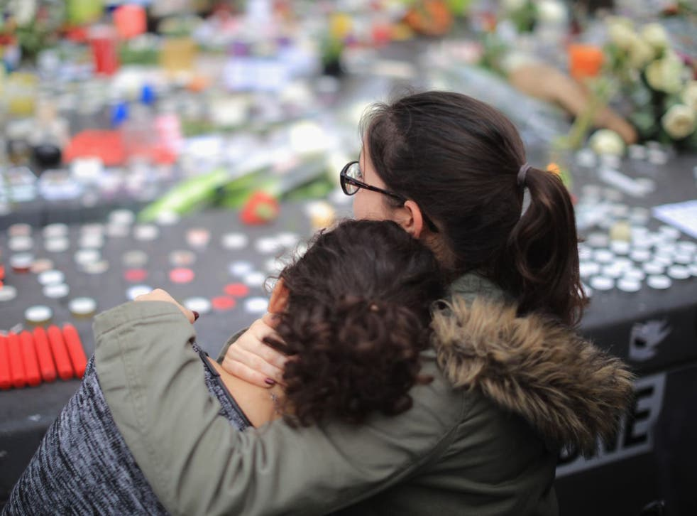 People weep as they gather to observe a minute-silence at the Place de la Republique in memory of the victims of the Paris terror attacks