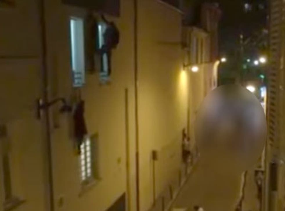 The video shows the woman hanging from a window ledge at the Bataclan theatre