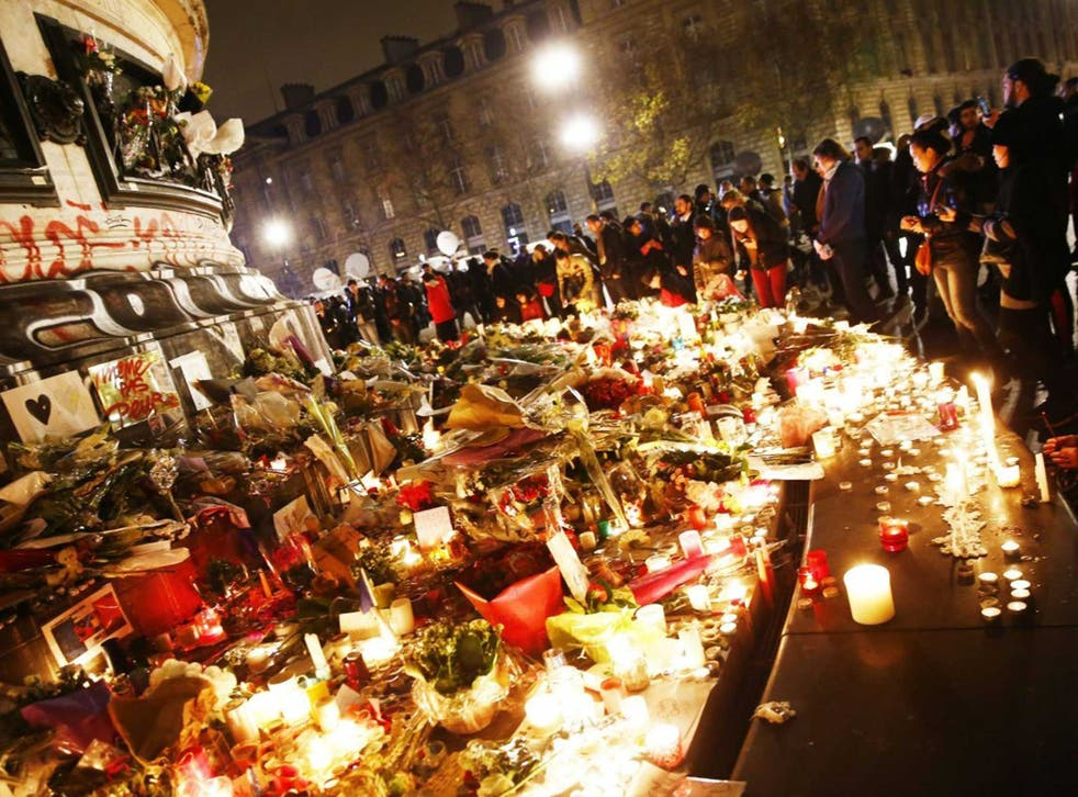People honouring the victims at Place de la Republique with flowers and candles