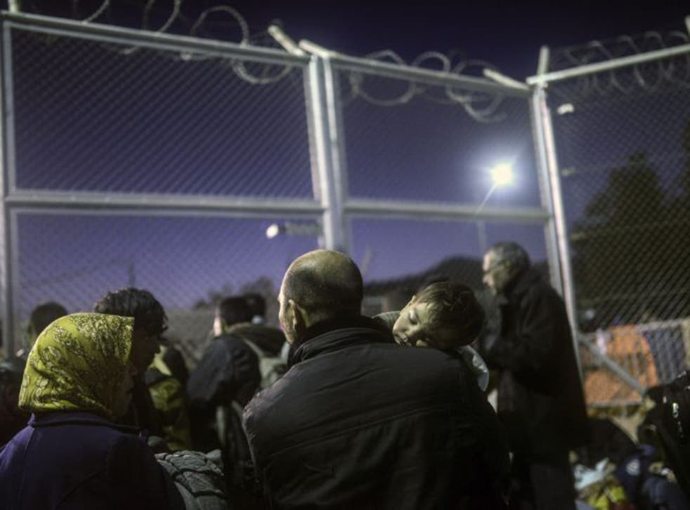 Refugees and migrants wait in front of a gate for registration in an a camp on the Greek island of Lesbos