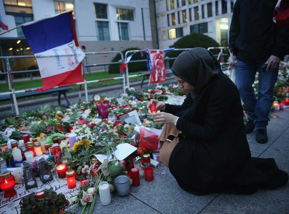 A woman pays tribute to the victims of the Paris attack