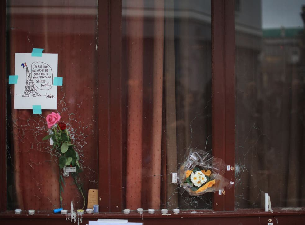 Flowers and tributes adorn the bullet damaged windows of the Le Carillon restaurant, one of the scenes of the November 16 attacks in Paris
