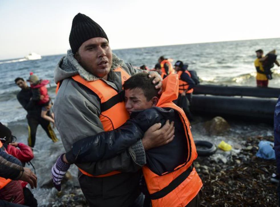 Refugees alight on the island of Lesbos after crossing the Aegean Sea from Turkey